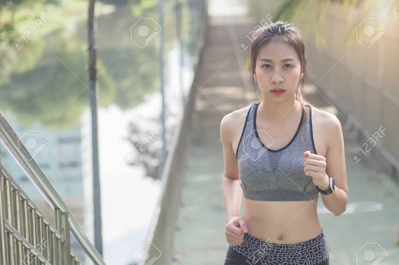 Young asian woman running on sidewalk in morning. Health conscious concept with copy space. Young sport asian woman running upstairs on city stairs. Fitness sport people and healthy lifestyle concept. - 93346276