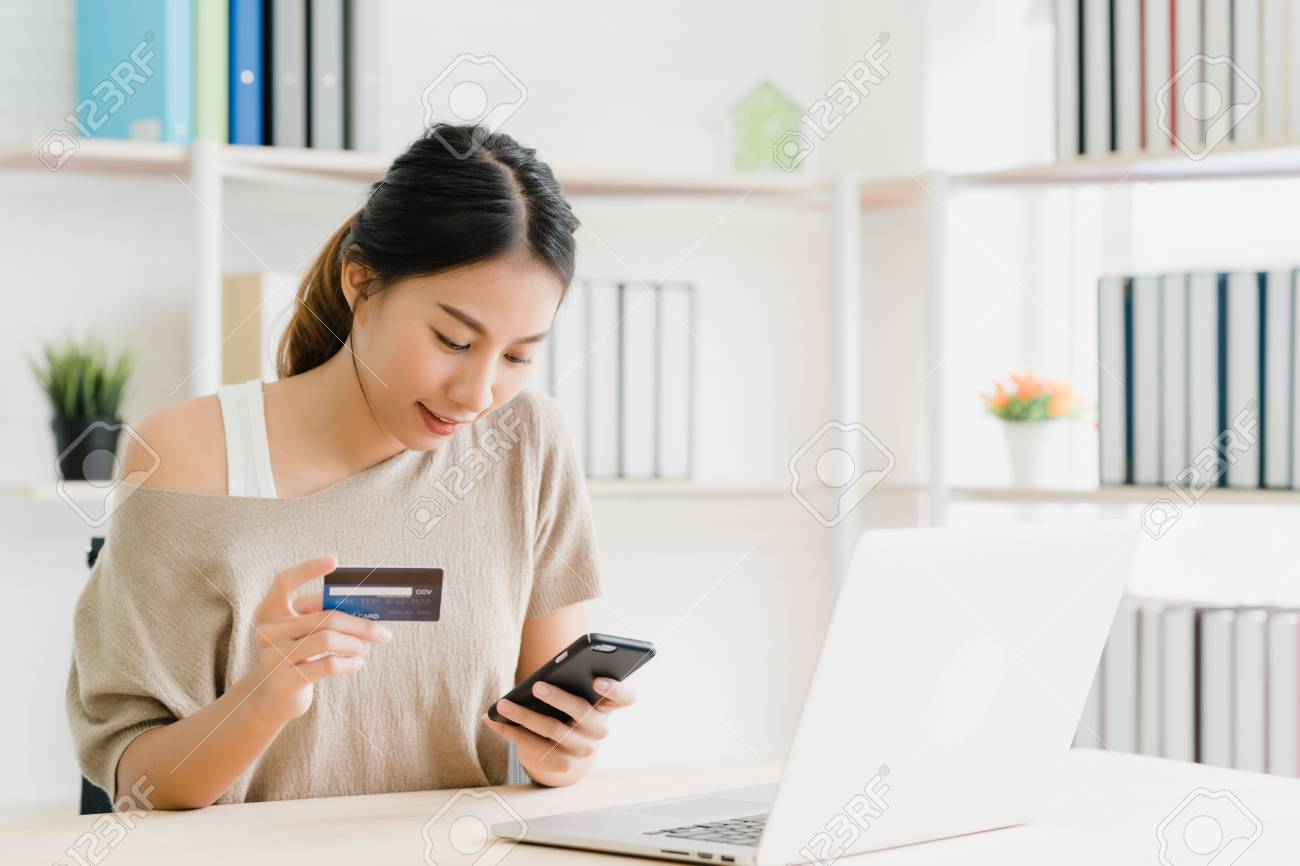Beautiful Asian woman using smartphone buying online shopping by credit card while wear sweater sitting on desk in living room at home. Lifestyle woman at home concept. - 120849404