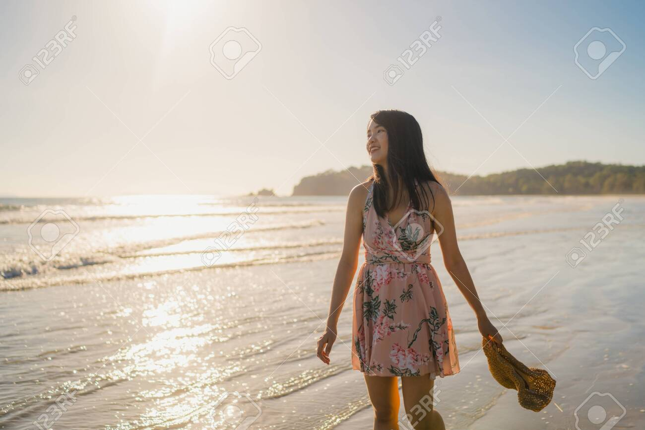 Young Asian woman walking on beach. Beautiful female happy relax walking on beach near sea when sunset in evening. Lifestyle women travel on beach concept. - 129915278