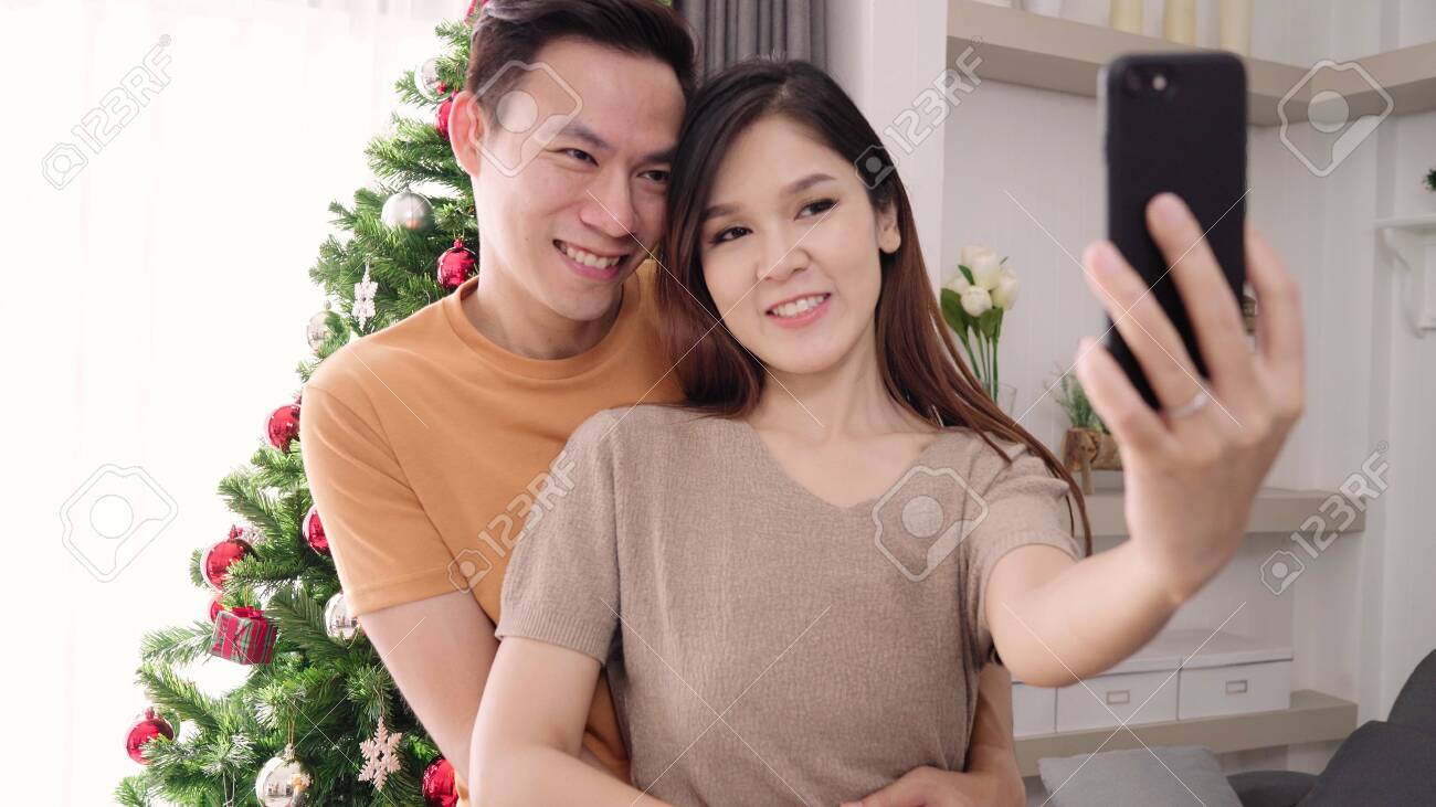 Asian Couple Using Smartphone Selfie With Christmas Tree Decorate Stock Photo Picture And Royalty Free Image Image 129944589