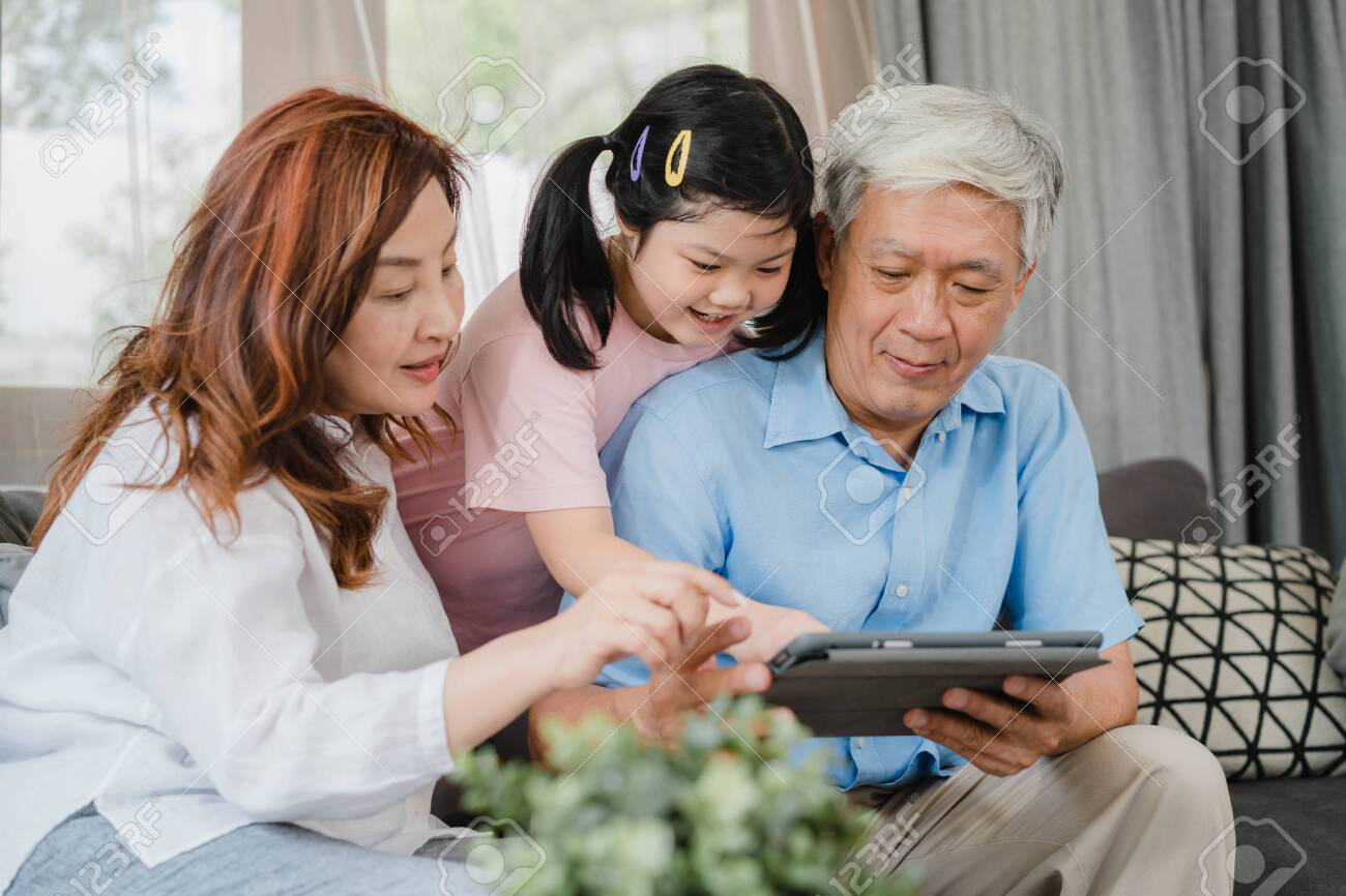 Asian grandparents and granddaughter using tablet at home. Senior Chinese, grandpa and grandma happy spend family time relax with young girl checking social media, lying on sofa in living room concept - 153592416