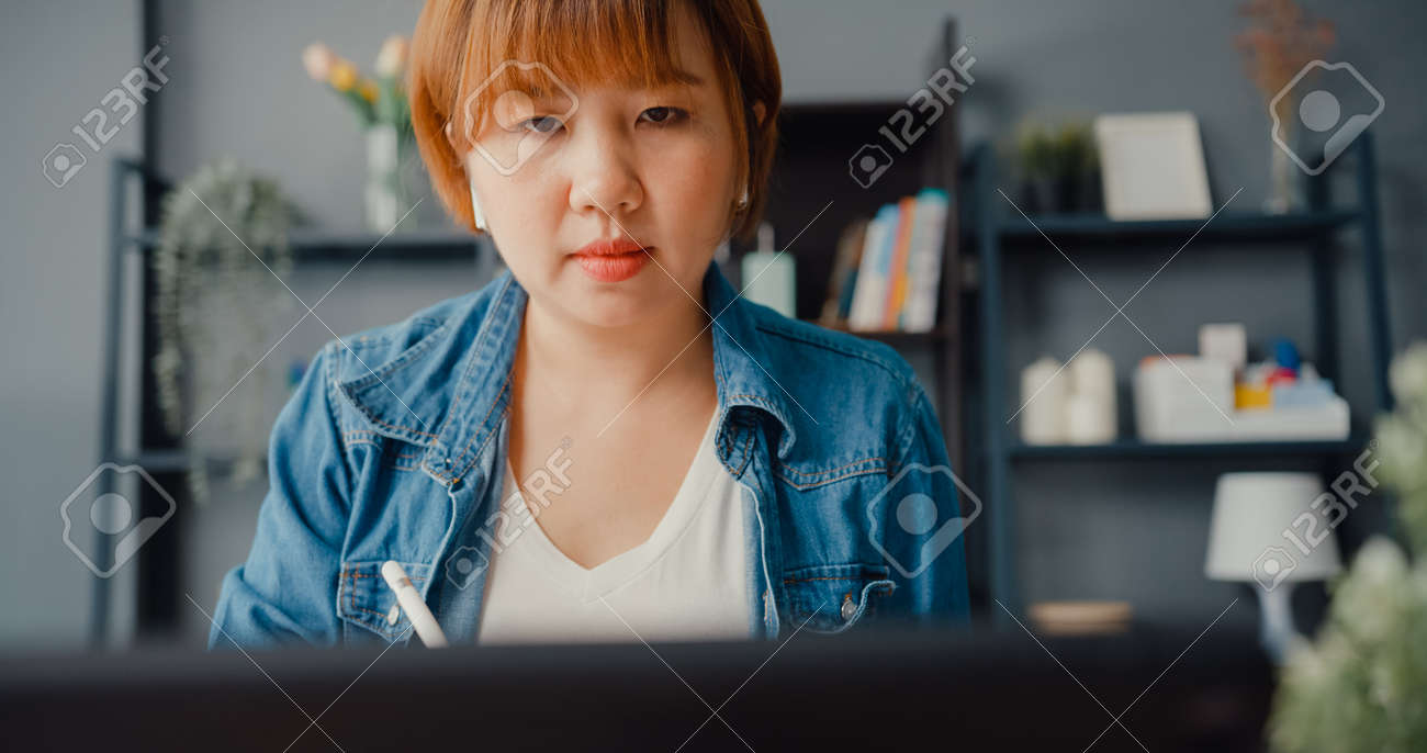 Asia businesswoman using tablet talk to colleagues about plan in video call while working from house at living room. Remotely at workplace, social distancing, quarantine for corona virus prevention. - 169421861