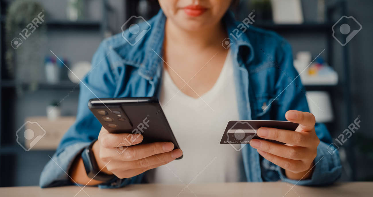 Young asia lady use cellphone order online shopping product and paying bills with credit card in living room interior. Stay at house, Self quarantine activity, Fun activity for coronavirus prevention. - 169421863