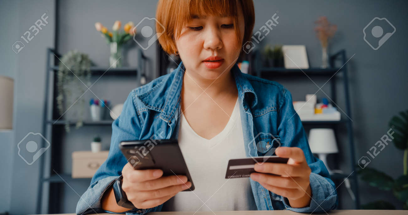 Young asia lady use cellphone order online shopping product and paying bills with credit card in living room interior. Stay at house, Self quarantine activity, Fun activity for coronavirus prevention. - 169421869