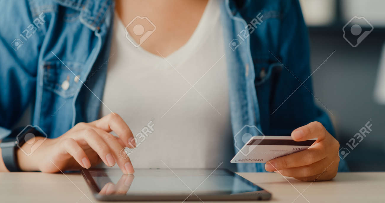 Young asia lady using tablet order online shopping product and paying bills with credit card in living room interior. Stay at house, Self quarantine activity, Fun activity for coronavirus prevention. - 169421872