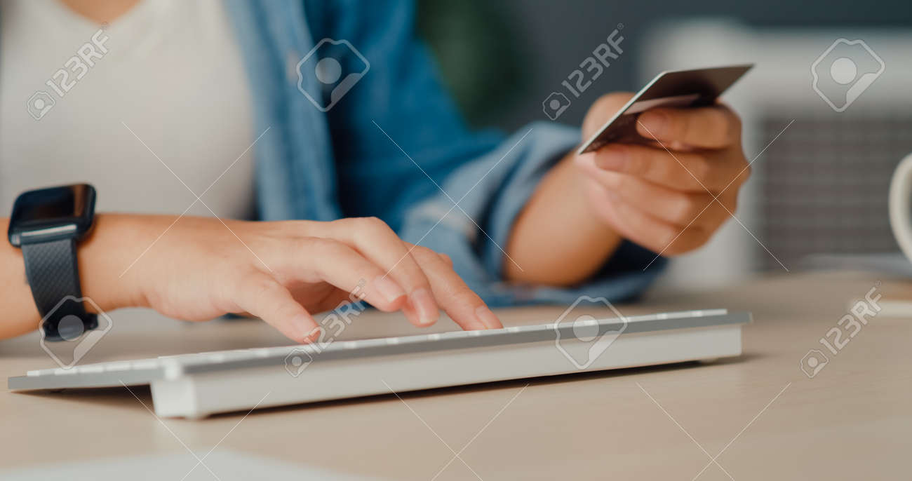 Young asia lady using computer order online shopping product and paying bill with credit card in living room interior. Stay at house, Self quarantine activity, Fun activity for coronavirus prevention. - 169421873