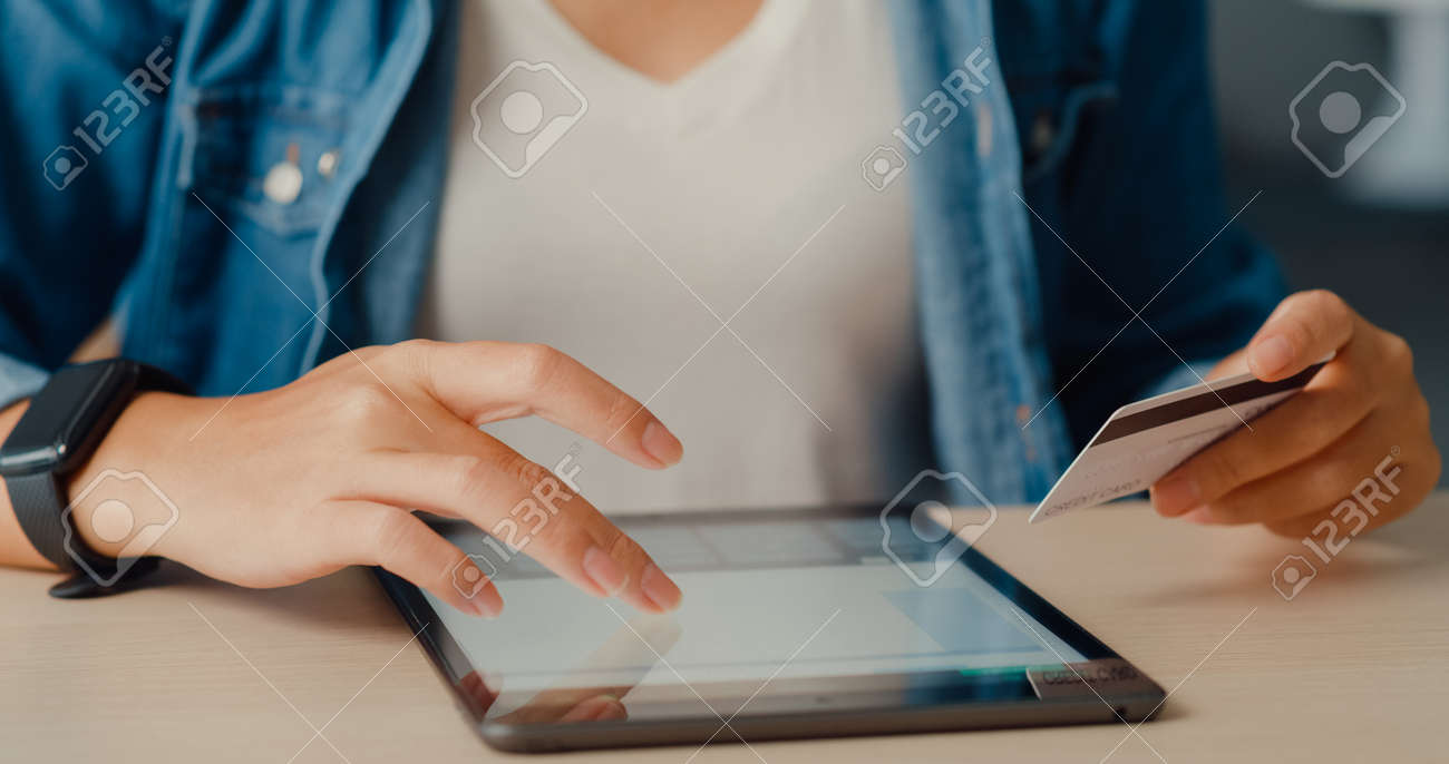 Young asia lady using tablet order online shopping product and paying bills with credit card in living room interior. Stay at house, Self quarantine activity, Fun activity for coronavirus prevention. - 169422723
