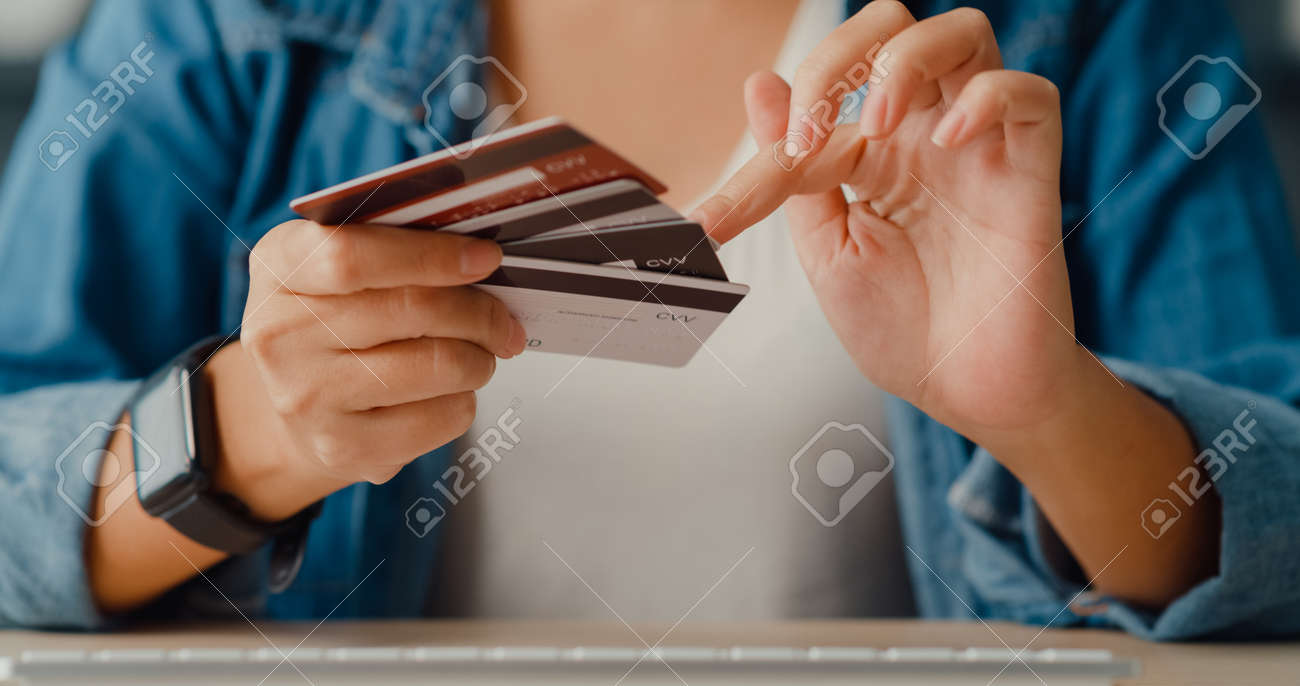 Young asia lady using computer order online shopping product and paying bill with credit card in living room interior. Stay at house, Self quarantine activity, Fun activity for coronavirus prevention. - 169422725