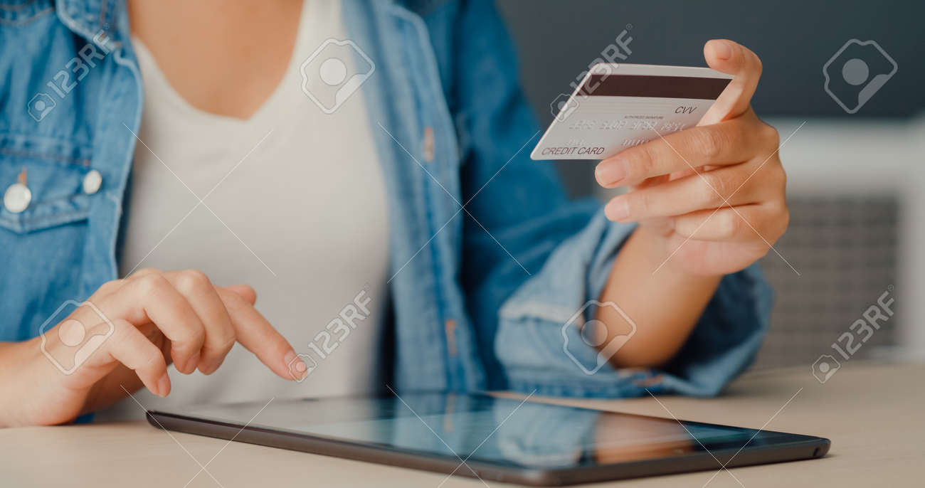 Young asia lady using tablet order online shopping product and paying bills with credit card in living room interior. Stay at house, Self quarantine activity, Fun activity for coronavirus prevention. - 169422726