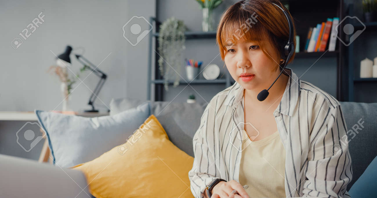 Asia businesswoman using laptop talk to colleagues about plan in video call while working from house at living room. Remotely at workplace, social distancing, quarantine for corona virus prevention. - 169422733