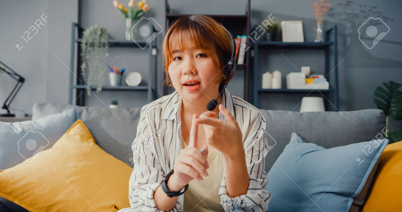 Asia businesswoman using laptop talk to colleagues about plan in video call while working from house at living room. Remotely at workplace, social distancing, quarantine for corona virus prevention. - 169422735
