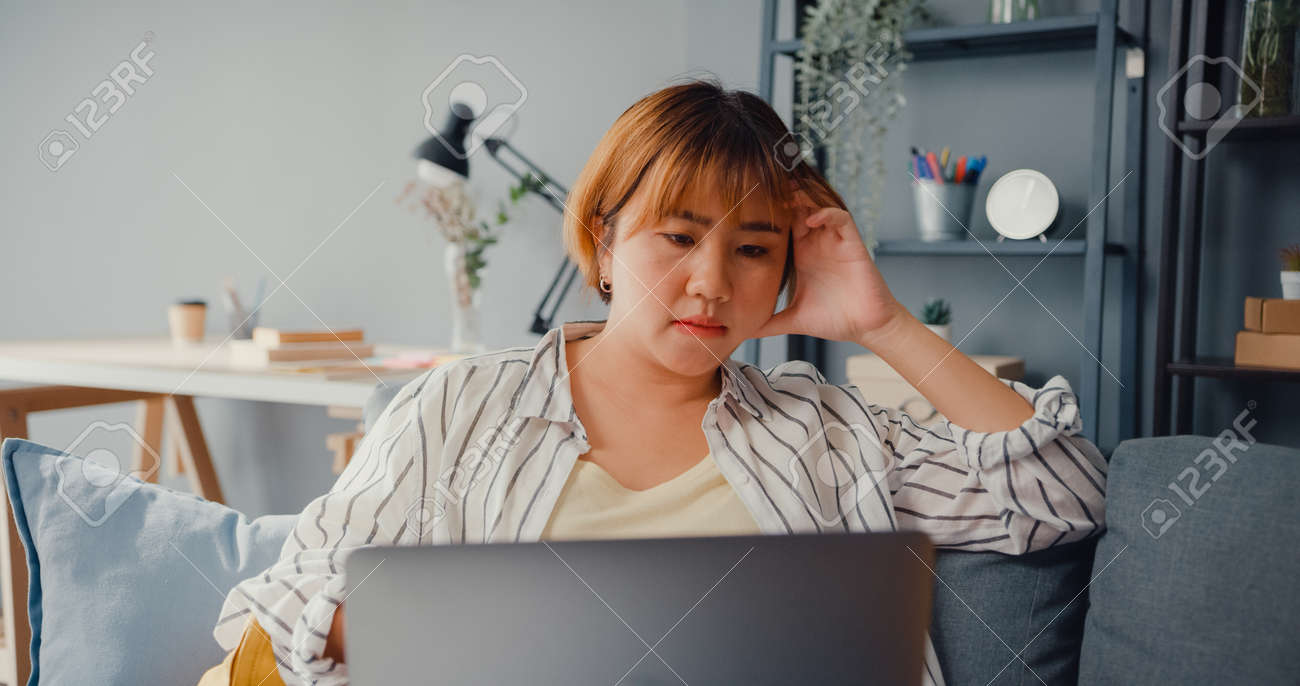 Freelance Asia lady feel headache while sitting on couch with laptop online learn in living room at house. Working from home, remotely work, social distancing, quarantine for corona virus prevention. - 169422738