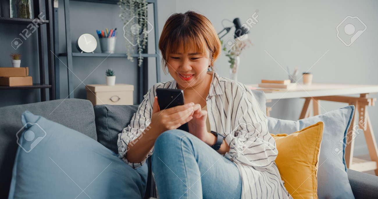 Young Asia lady using smartphone text message or check social media on sofa in living room at house. Work from home, play game, shopping online, social distance, quarantine for coronavirus prevention. - 169422740
