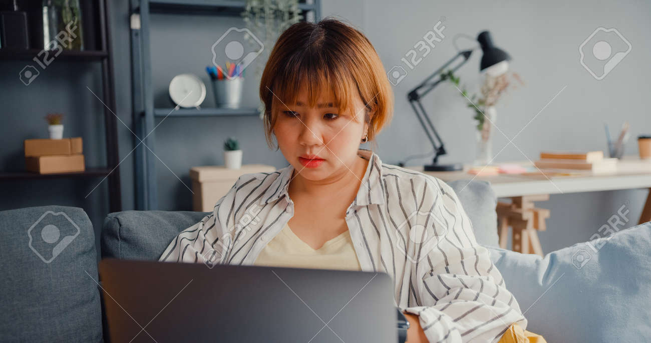 Freelance Asia lady feel headache while sitting on couch with laptop online learn in living room at house. Working from home, remotely work, social distancing, quarantine for corona virus prevention. - 169422743