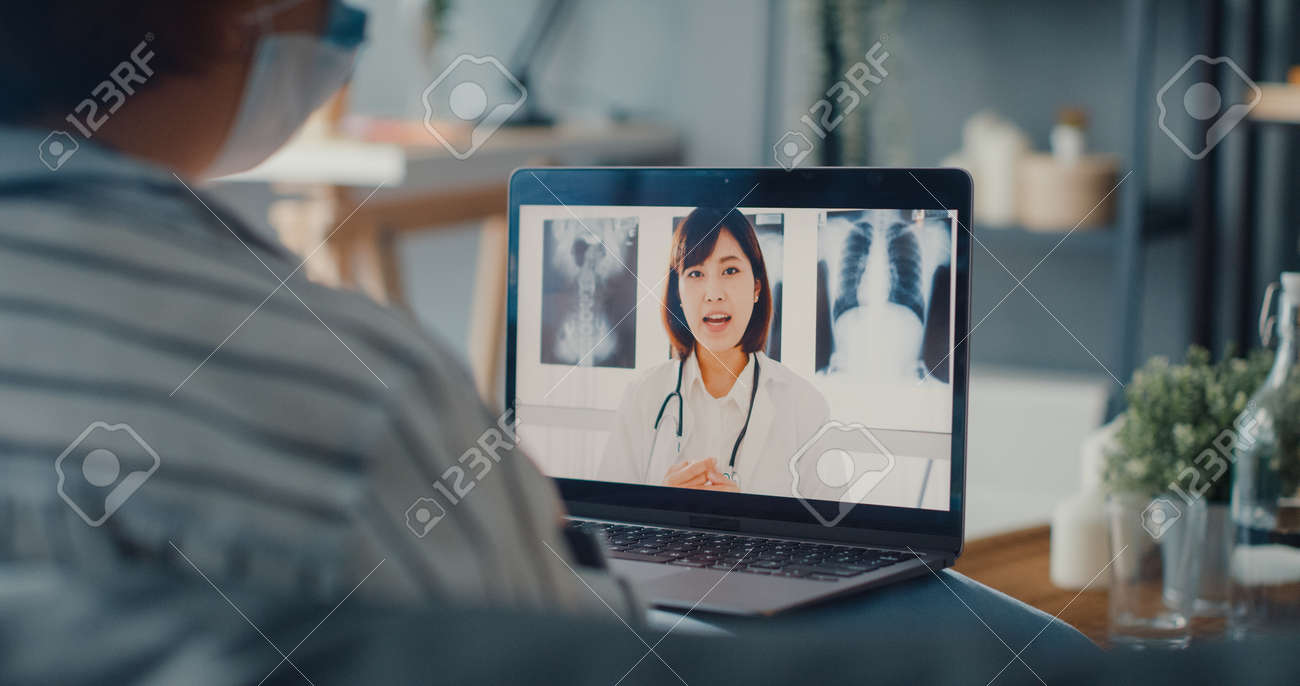 Young Asia girl wear protective face mask using laptop talk about disease in video call with senior doctor online consultation in living room at house. Social distancing, quarantine for coronavirus. - 169422862