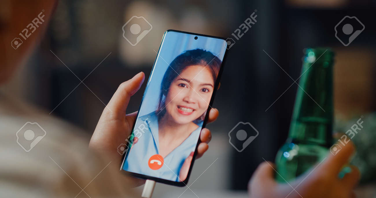 Youth Asia teen girl drink beer having fun happy moment night party event online celebration via video call in living room at house at night. Social distancing, quarantine for coronavirus prevention. - 169422872