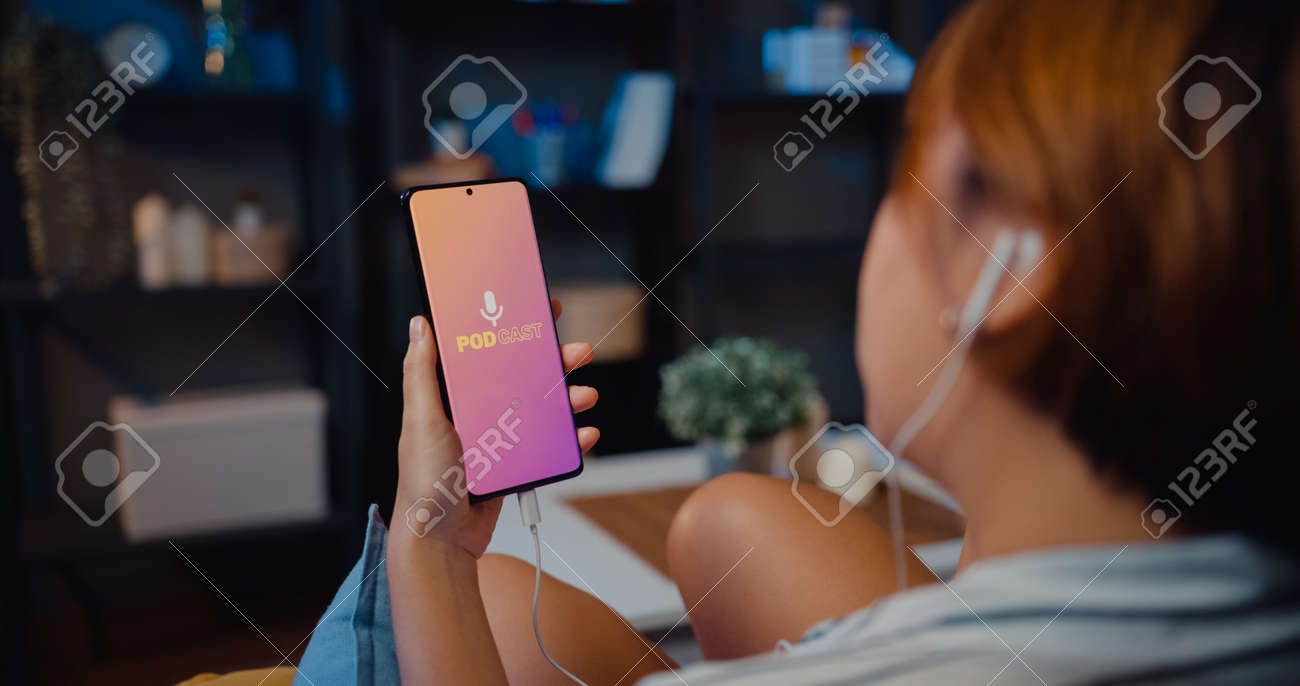 Young attractive Asia lady wear headphones using phone listen digital music podcast online channel sit on sofa in living room at house night. Social distancing, quarantine for coronavirus prevention. - 169422873
