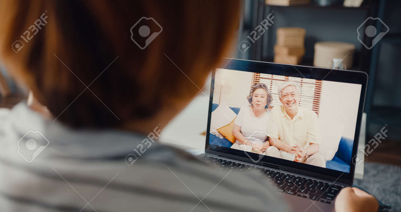 Young Asia girl using laptop video call meeting talk with elderly family dad and mom while work from home sitting on sofa at living room. Social distancing, quarantine for corona virus prevention. - 169422874