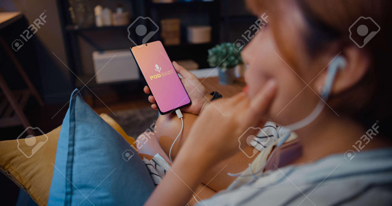 Young attractive Asia lady wear headphones using phone listen digital music podcast online channel sit on sofa in living room at house night. Social distancing, quarantine for coronavirus prevention. - 169422875
