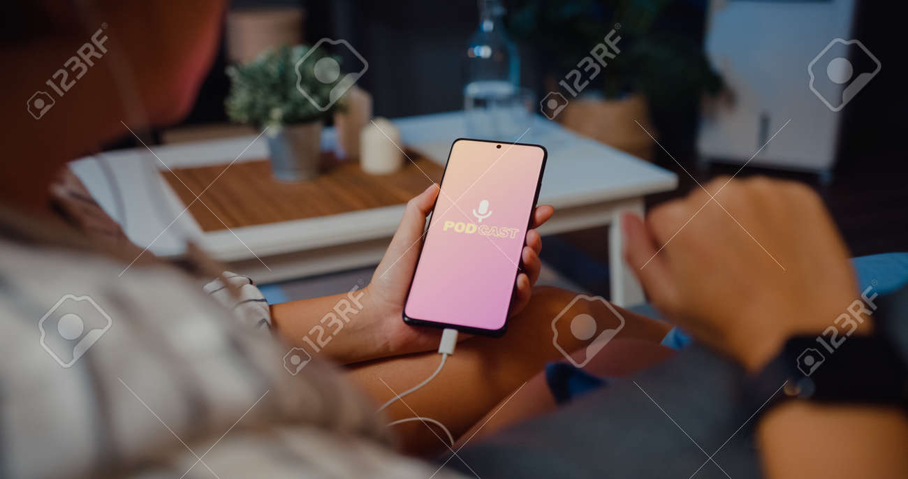 Young attractive Asia lady wear headphones using phone listen digital music podcast online channel sit on sofa in living room at house night. Social distancing, quarantine for coronavirus prevention. - 169422882