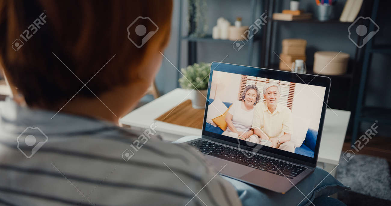 Young Asia girl using laptop video call meeting talk with elderly family dad and mom while work from home sitting on sofa at living room. Social distancing, quarantine for corona virus prevention. - 169422884