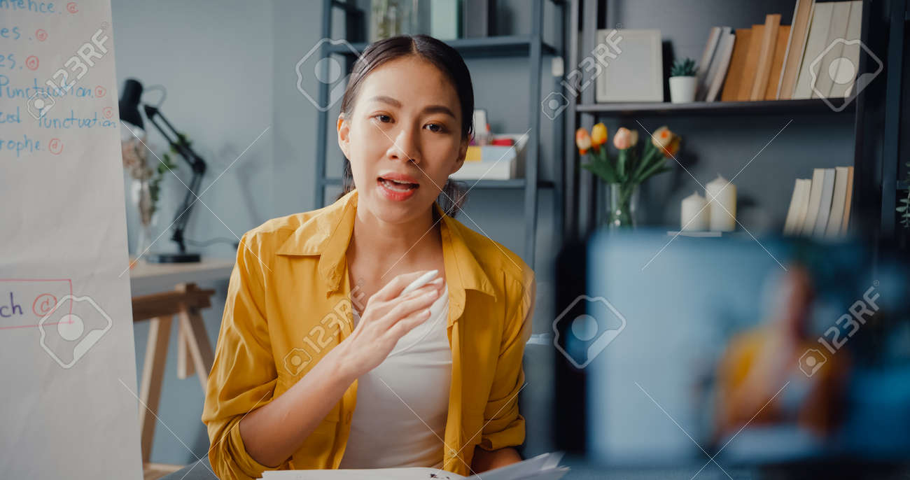 Young Asia lady english teacher video conference calling on smartphone talk by webcam learn teach in online chat at home. Remote classroom, Social distancing, quarantine for corona virus prevention. - 169422885