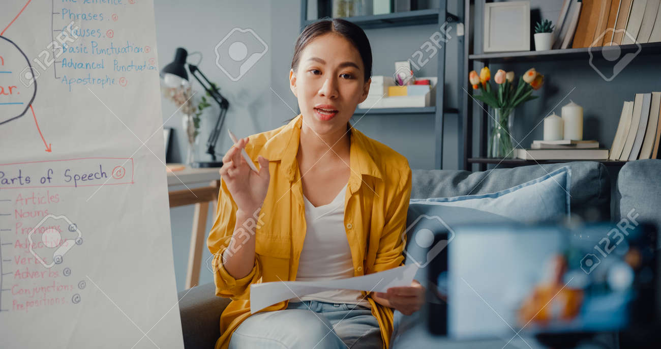 Young Asia lady english teacher video conference calling on smartphone talk by webcam learn teach in online chat at home. Remote classroom, Social distancing, quarantine for corona virus prevention. - 169422886
