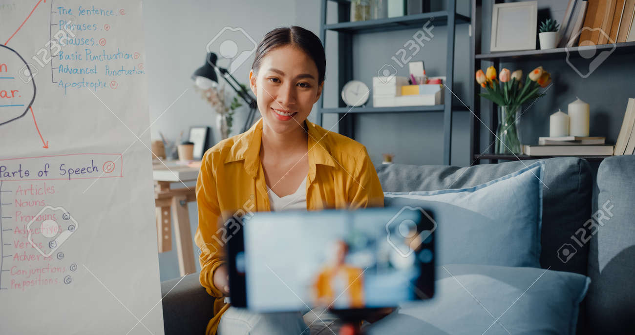 Young Asia lady english teacher video conference calling on smartphone talk by webcam learn teach in online chat at home. Remote classroom, Social distancing, quarantine for corona virus prevention. - 169422888