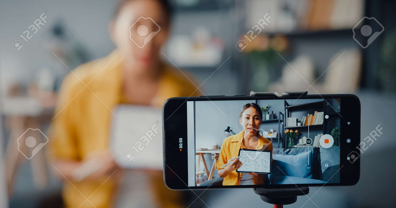 Young Asia lady teacher video call on smartphone talk by webcam learn teach in online chat at home. Remote school class, Social distancing, quarantine for corona virus prevention. Close up screen. - 169422896