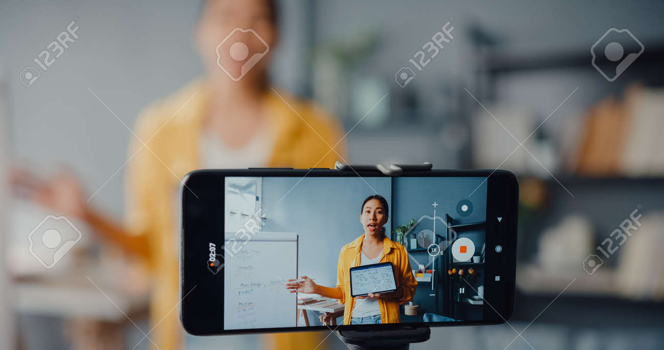 Young Asia lady teacher video call on smartphone talk by webcam learn teach in online chat at home. Remote school class, Social distancing, quarantine for corona virus prevention. Close up screen. - 169422897