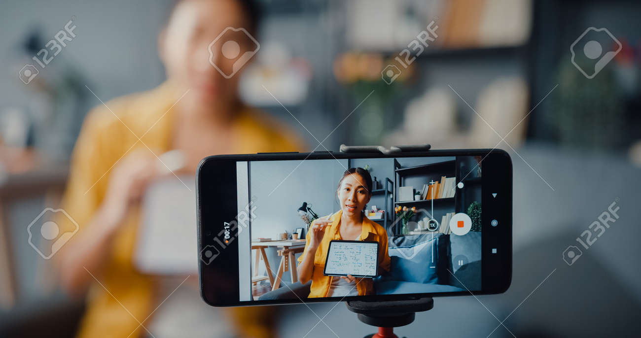 Young Asia lady teacher video call on smartphone talk by webcam learn teach in online chat at home. Remote school class, Social distancing, quarantine for corona virus prevention. Close up screen. - 169422977