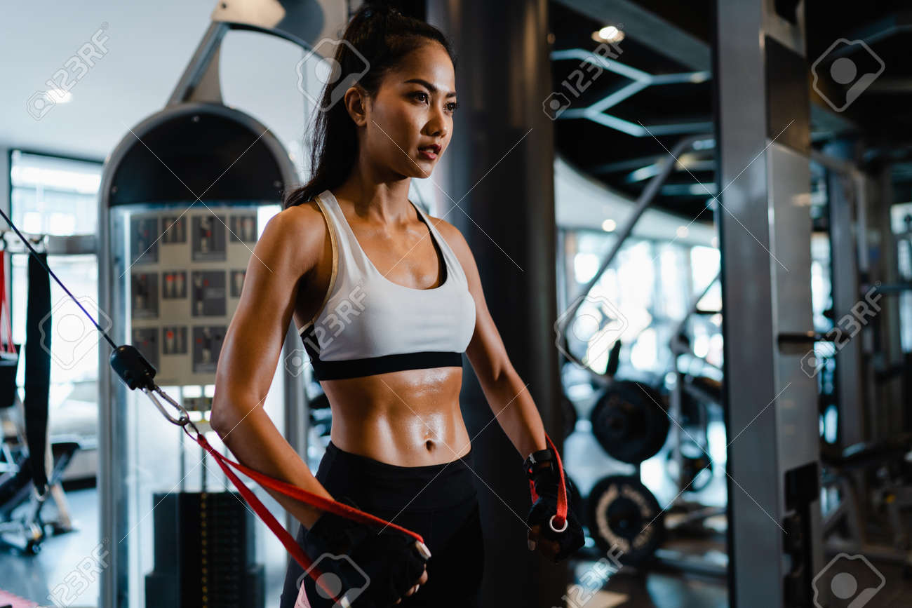 Young Asia lady exercise doing exercise-machine Cable Crossover fat burning workout in fitness class. Athlete with six pack, Sportswoman recreational activity, functional training, healthy lifestyle. - 169422982