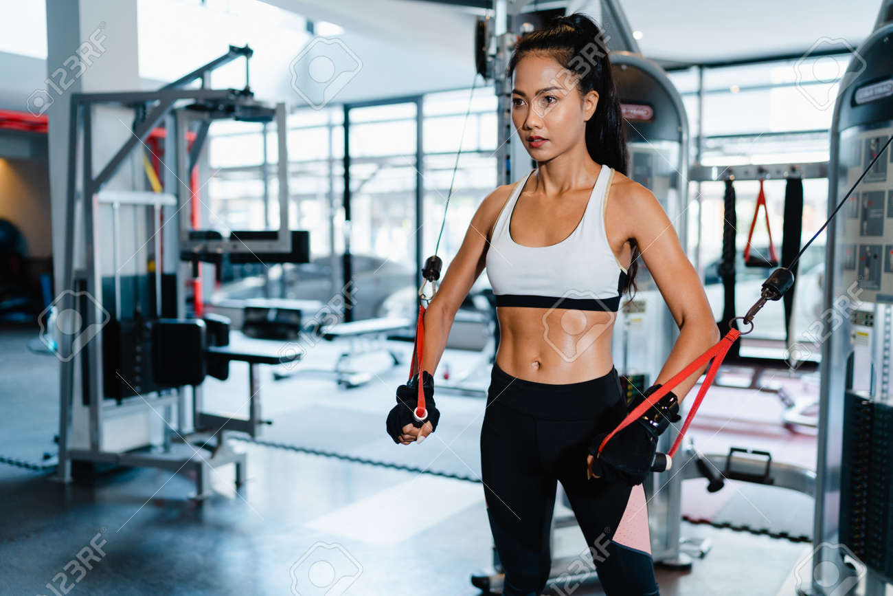 Young Asia lady exercise doing exercise-machine Cable Crossover fat burning workout in fitness class. Athlete with six pack, Sportswoman recreational activity, functional training, healthy lifestyle. - 169422983