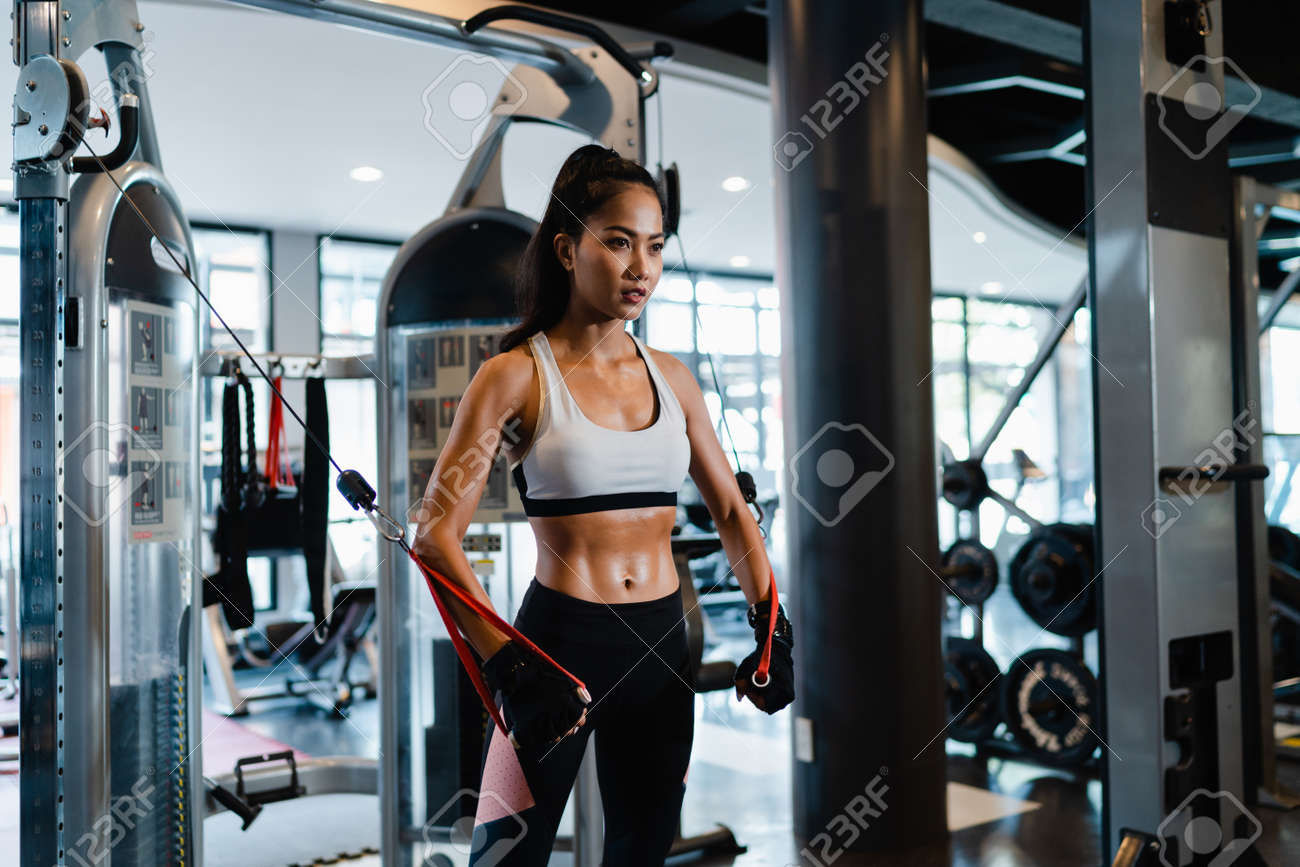 Young Asia lady exercise doing exercise-machine Cable Crossover fat burning workout in fitness class. Athlete with six pack, Sportswoman recreational activity, functional training, healthy lifestyle. - 169422984