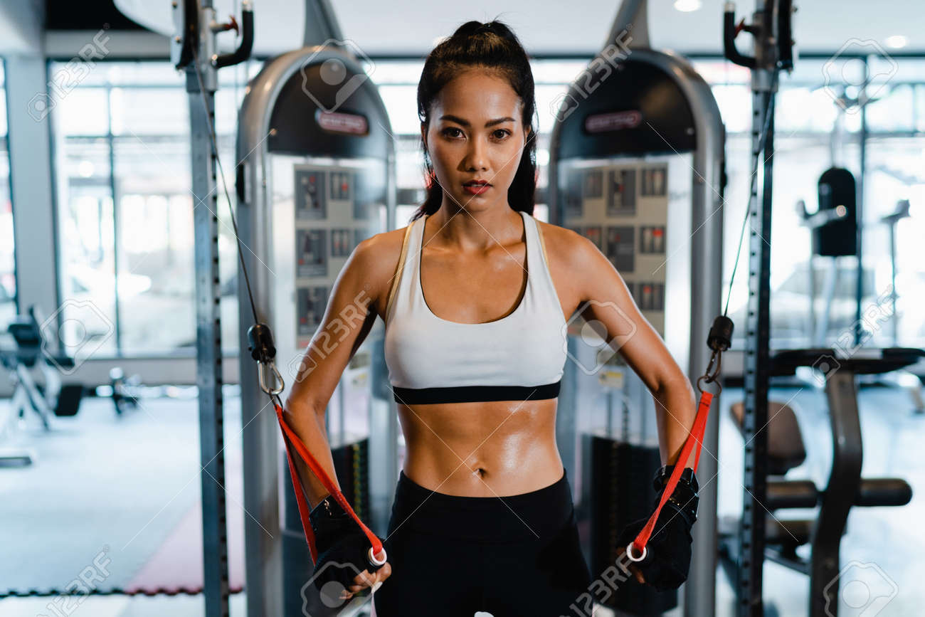 Young Asia lady exercise doing exercise-machine Cable Crossover fat burning workout in fitness class. Athlete with six pack, Sportswoman recreational activity, functional training, healthy lifestyle. - 169422985