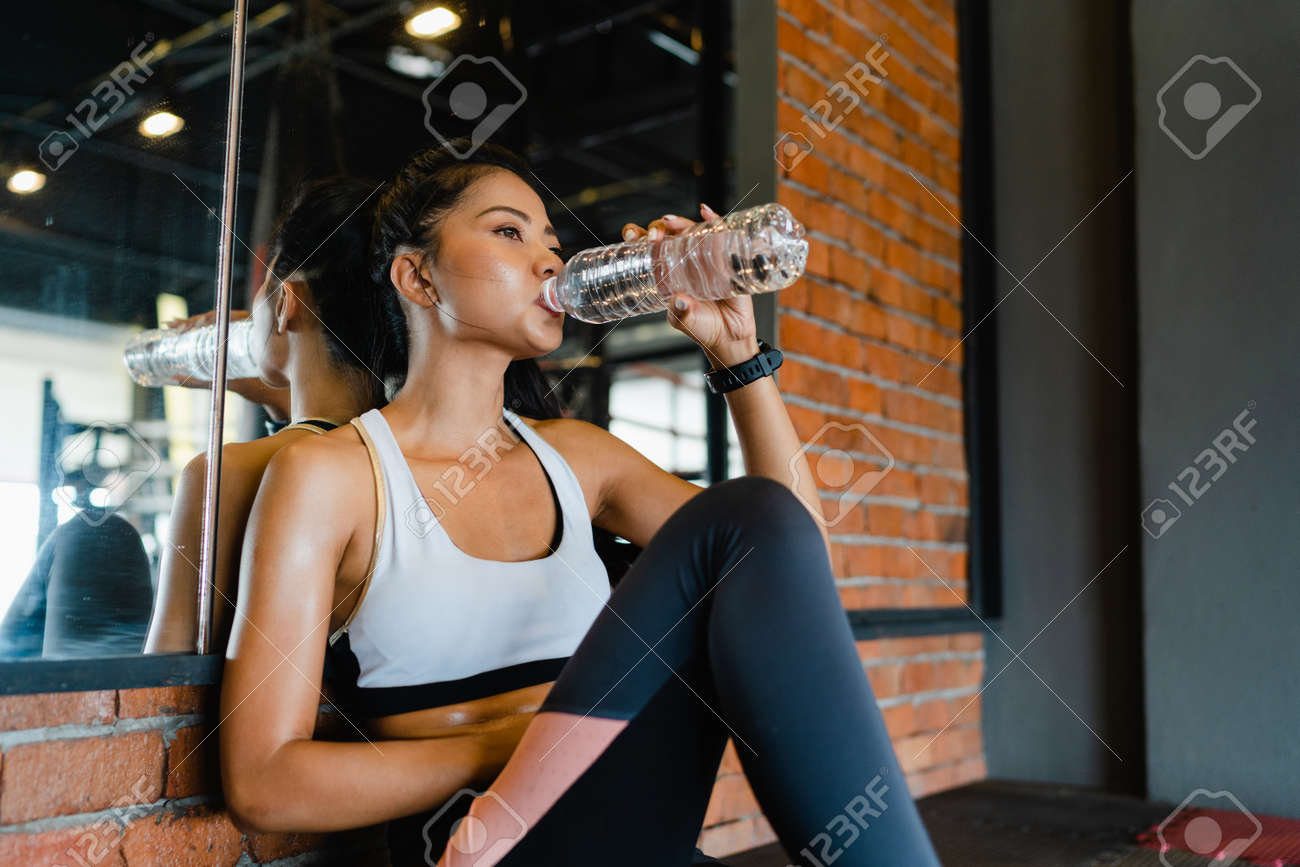 Beautiful young Asia lady exercise drinking water after fat burning workout in fitness class. Athlete with six pack, Sportswoman recreational activity, functional training, healthy lifestyle concept. - 169422986
