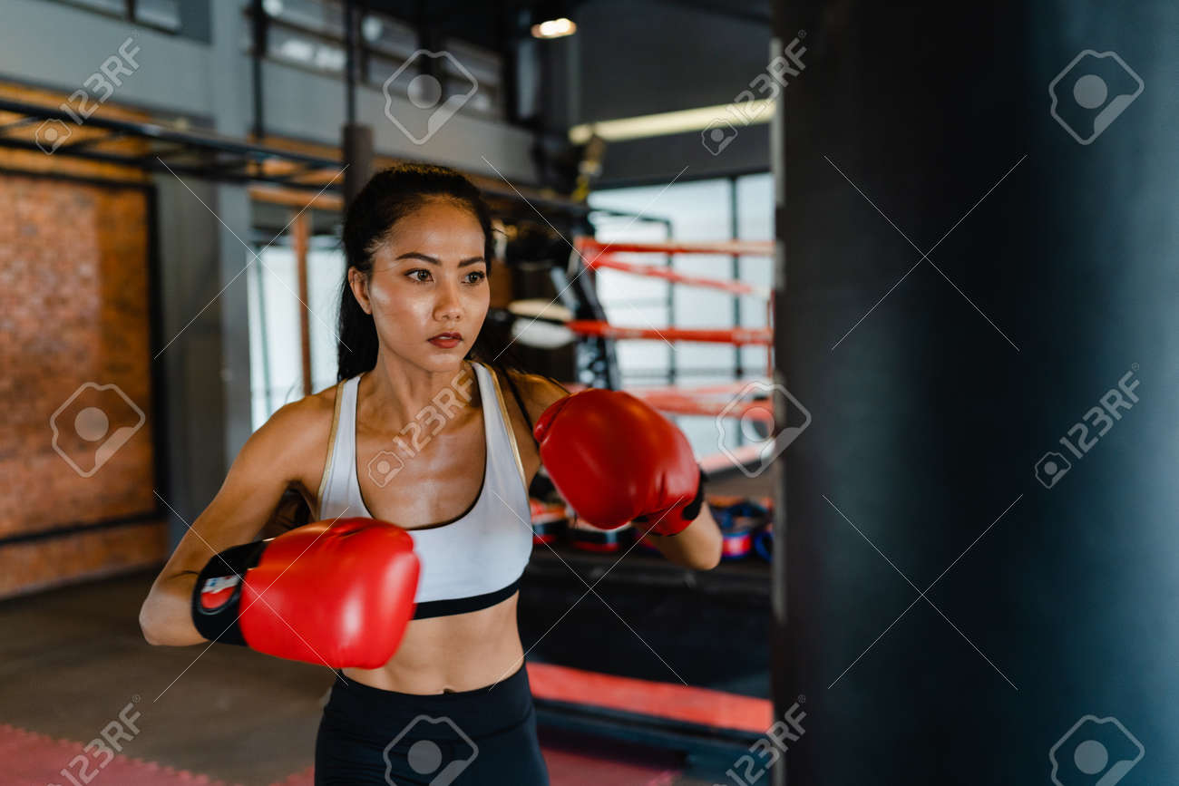 Young Asia lady kickboxing exercise workout punching bag tough female fighter practice boxing in gym fitness class. Sportswoman recreational activity, functional training, healthy lifestyle concept. - 169422987