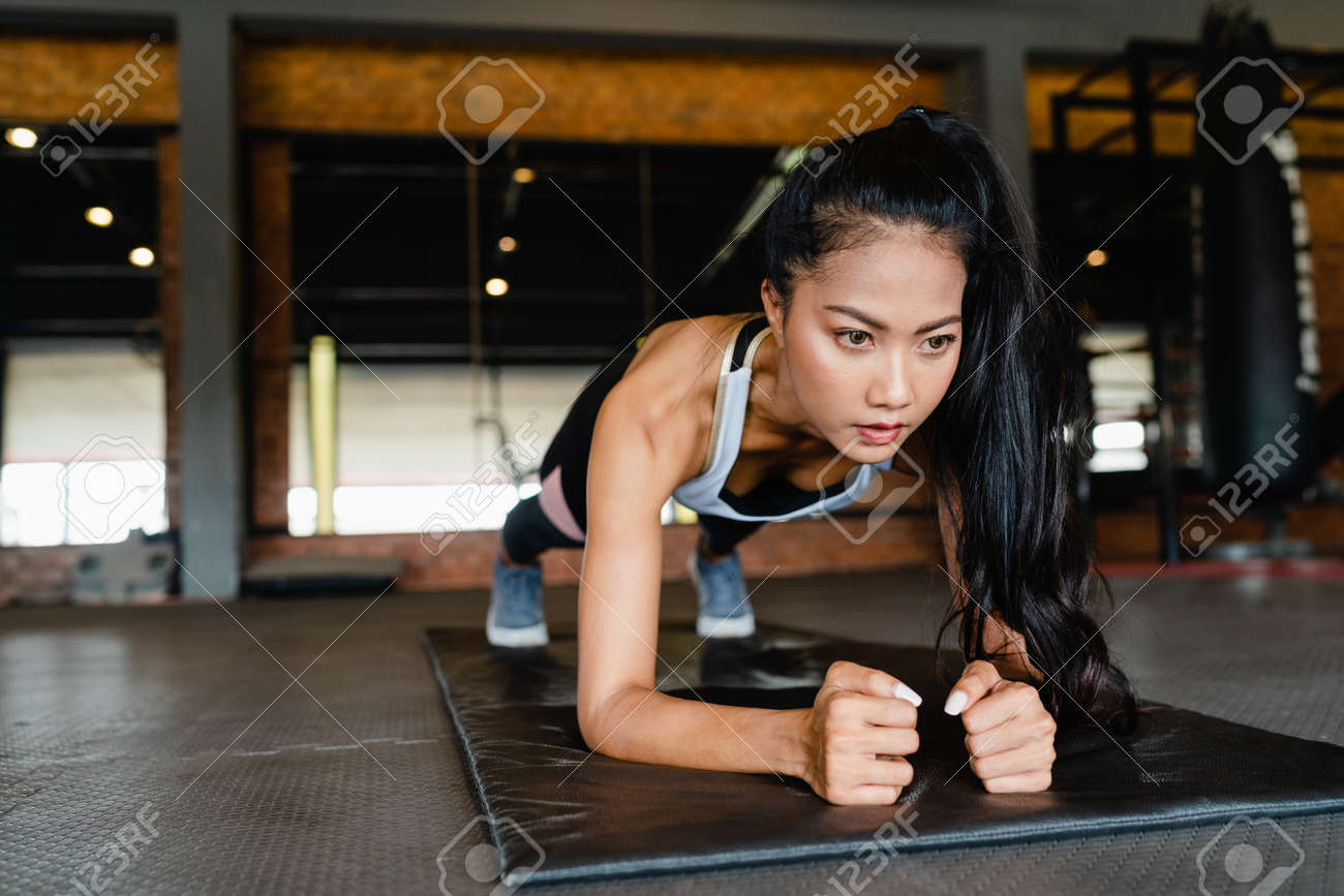 Happy young Asia lady exercise doing plank fat burning workout in fitness class. Athlete with six pack, Sportswoman recreational activity, functional training, healthy lifestyle concept. - 169422988