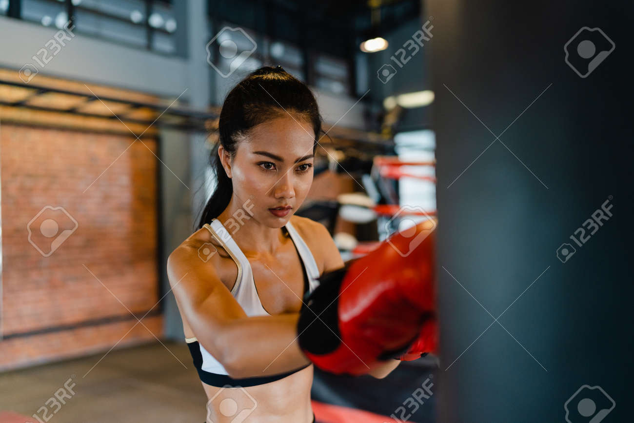 Young Asia lady kickboxing exercise workout punching bag tough female fighter practice boxing in gym fitness class. Sportswoman recreational activity, functional training, healthy lifestyle concept. - 169422992