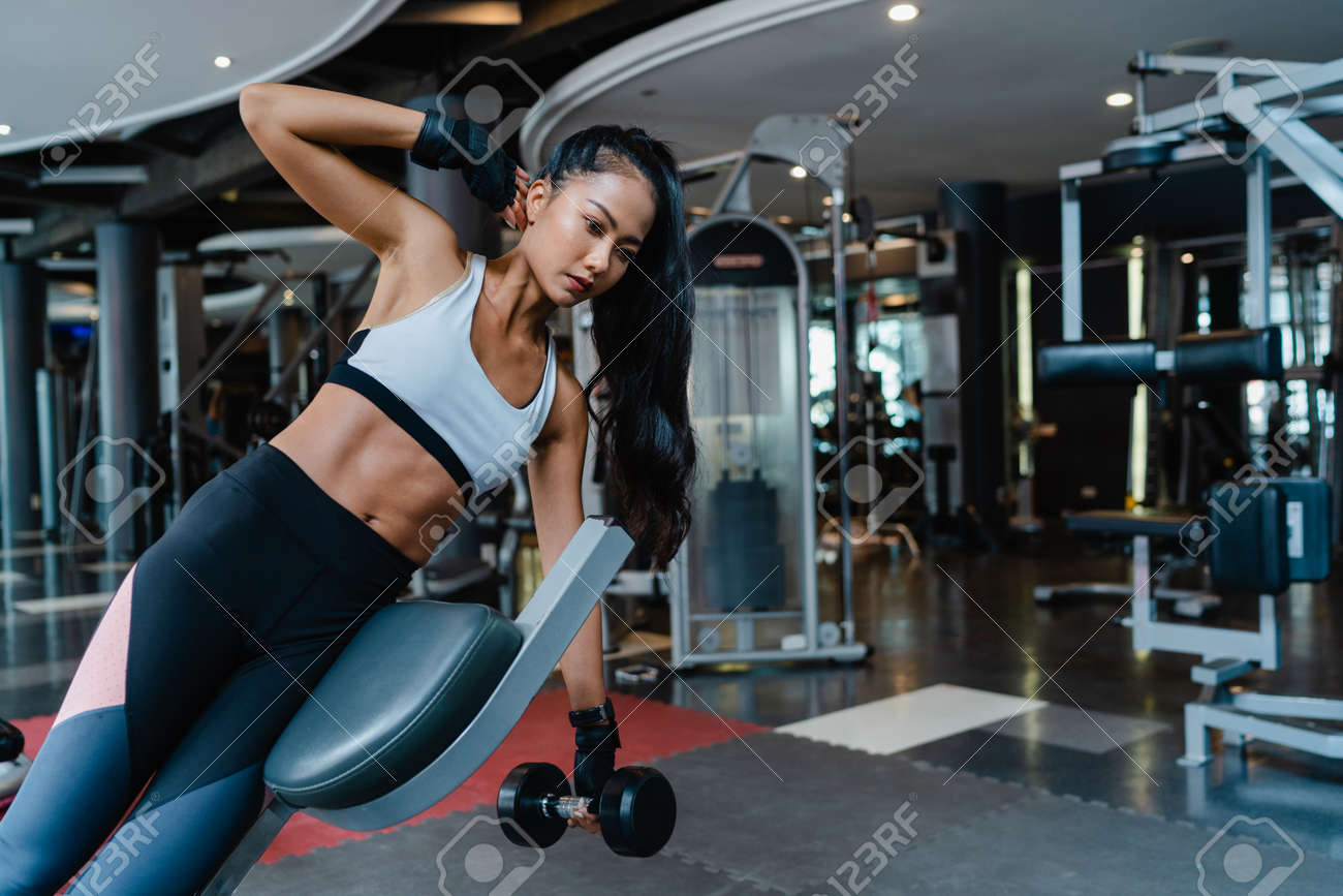 Beautiful young Asia lady exercise doing lifting barbell fat burning workout in fitness class. Athlete with six pack, Sportswoman recreational activity, functional training, healthy lifestyle concept. - 169422993
