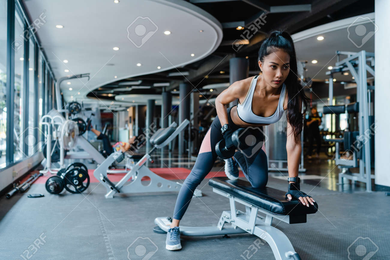Beautiful young Asia lady exercise doing lifting barbell fat burning workout in fitness class. Athlete with six pack, Sportswoman recreational activity, functional training, healthy lifestyle concept. - 169422995