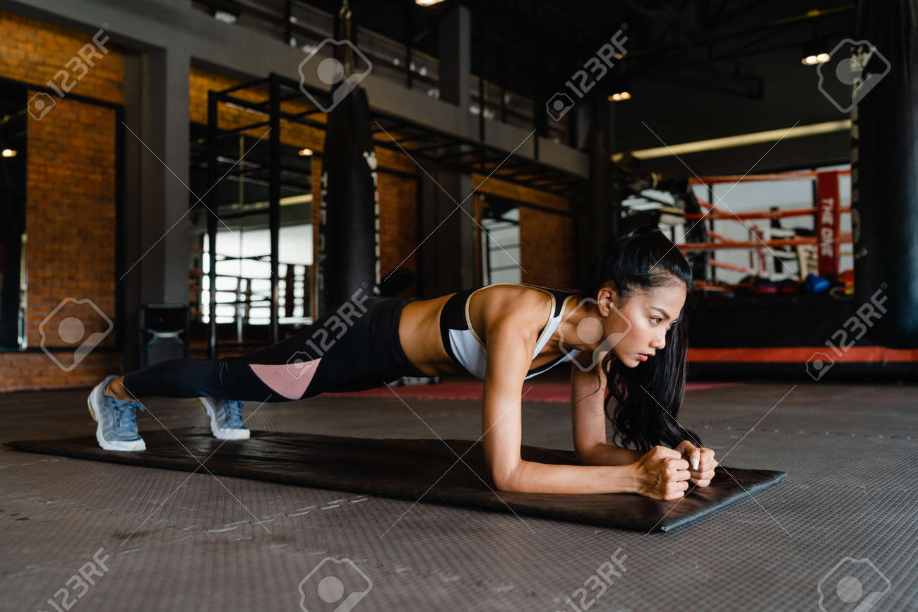 Happy young Asia lady exercise doing plank fat burning workout in fitness class. Athlete with six pack, Sportswoman recreational activity, functional training, healthy lifestyle concept. - 169422998