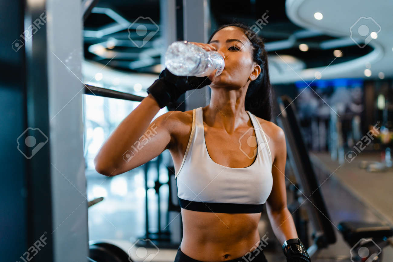 Beautiful young Asia lady exercise drinking water after fat burning workout in fitness class. Athlete with six pack, Sportswoman recreational activity, functional training, healthy lifestyle concept. - 169423002