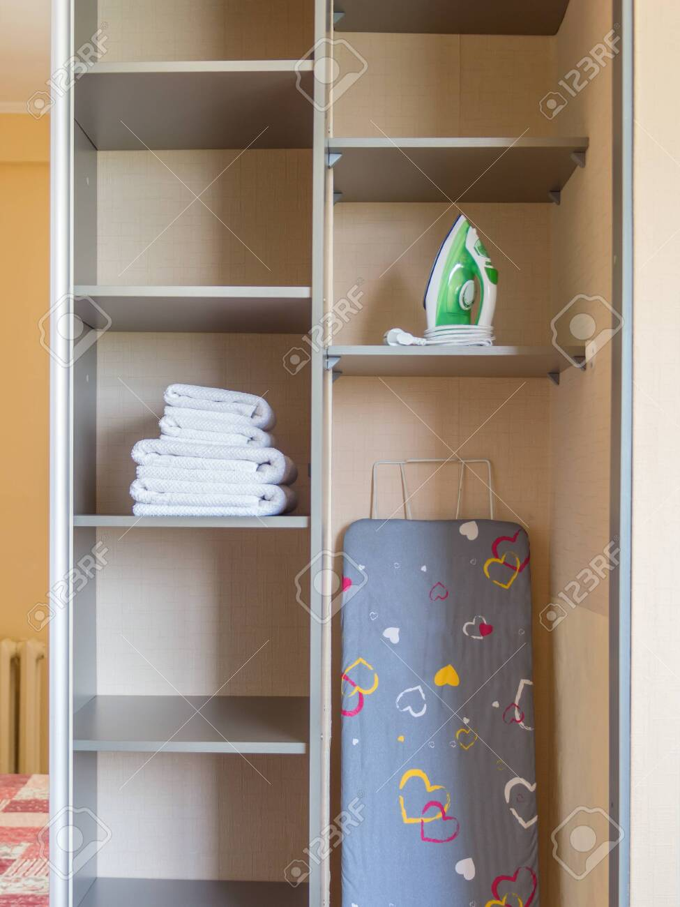 Ironing board, iron, clean towels at closet - 144347315