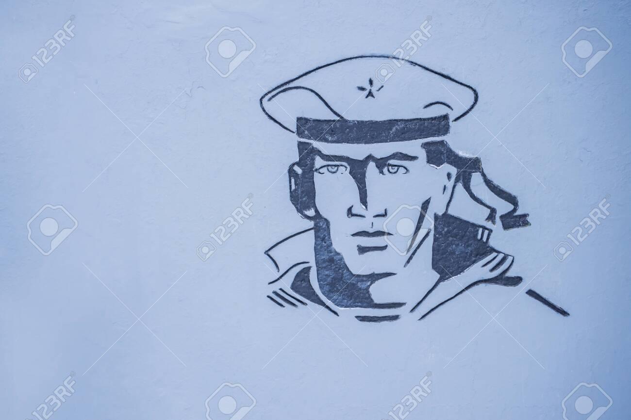 Image of a sailor at a war memorial, on a gray wall - 144546254