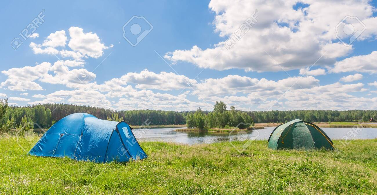Two tourist tents on the lake in summer - 146768795