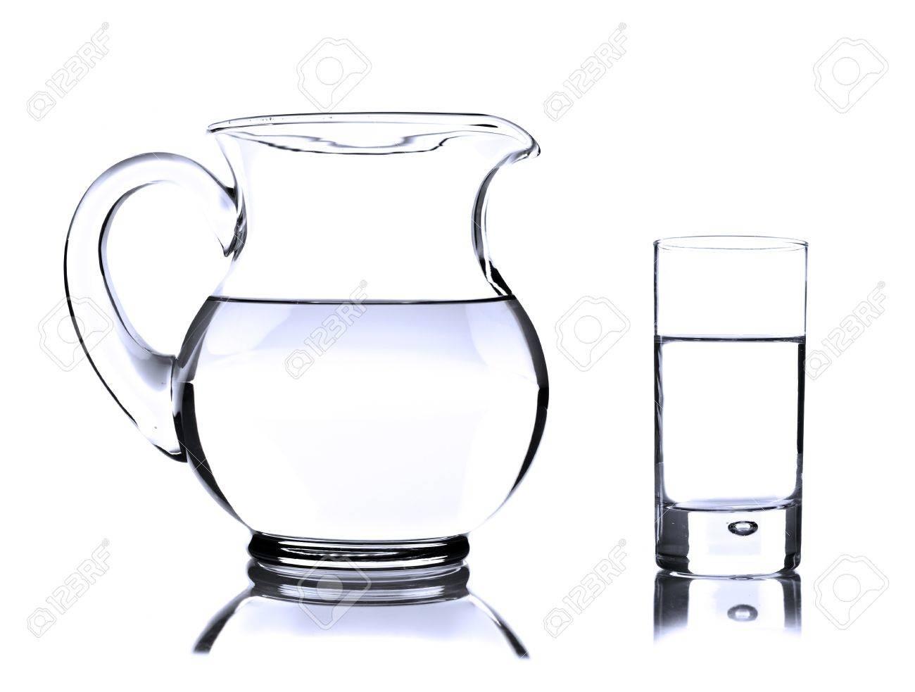 jarra de vidrio y vaso con agua sobre fondo blanco foto de archivo