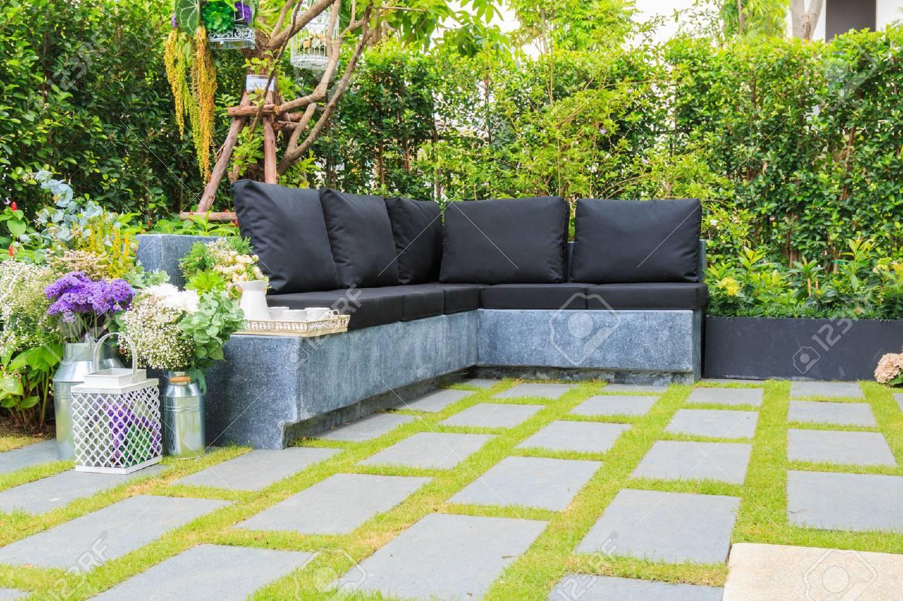 Tè impostato su una panchina di pietra in un giardino di fiori. foto