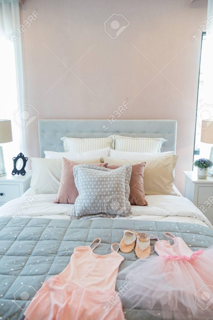 Ballett Set Und Viele Kissen Auf Einem Mädchen Bett Mit Nachttischlampe In  Warmes Licht Schlafzimmer