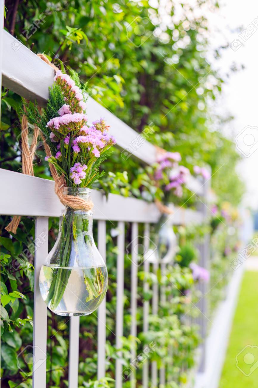 A Purple Flowers In Light Bulb Shaped Vase Hanging On Home Fence